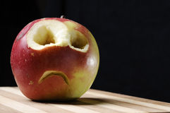 Trauriger gegenübergestellter Apfel auf hölzernem Vorstand Stockbild