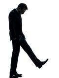 Trauriger Geschäftsmann, der hinunter Schattenbild schaut Lizenzfreies Stockfoto