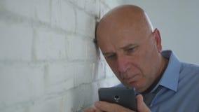 Trauriger Geschäftsmann im Büro-Text unter Verwendung des Handy-drahtlosen Netzwerks lizenzfreie stockfotografie