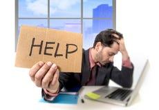 Trauriger Geschäftsmann am Schreibtisch, der an Computerlaptop bitten um Hilfe niedergedrückt arbeitet Stockfoto