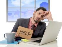 Trauriger Geschäftsmann am Schreibtisch, der an Computerlaptop bitten um Hilfe niedergedrückt arbeitet Stockbild