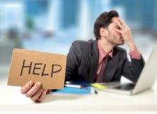 Trauriger Geschäftsmann am Schreibtisch, der an Computerlaptop bitten um Hilfe niedergedrückt arbeitet Stockfotos
