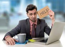Trauriger Geschäftsmann am Schreibtisch, der an Computerlaptop bitten um Hilfe niedergedrückt arbeitet Lizenzfreies Stockfoto