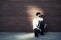 Trauriger Geschäftsmann in der Krise, die an der Wand sitzt Stockfoto