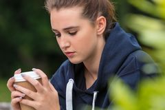 Trauriger Jugendlich-junge Frauen-trinkender Kaffee draußen Stockfotografie