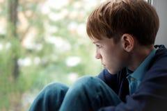 Trauriger Jugendlicher, der auf Fenster sitzt Stockbilder
