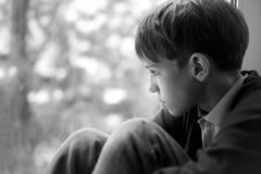 Trauriger Jugendlicher, der auf Fenster sitzt Lizenzfreie Stockfotos