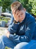 Trauriger Jugendlicher, der auf Straße sitzt stockfoto