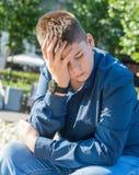 Trauriger Jugendlicher, der auf Straße sitzt lizenzfreie stockfotografie