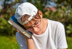 Trauriger Jugendlicher mit einem Buch stockbild