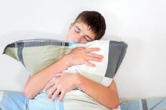 Trauriger Jugendlicher mit Kissen Stockbild