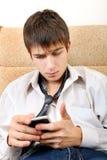 Trauriger Jugendlicher mit Mobiltelefon Stockbild