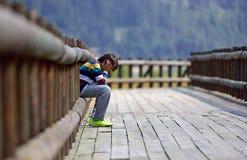 Trauriger Junge, der allein sitzt Stockbild