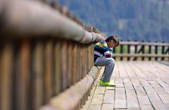 Trauriger Junge, der allein sitzt Stockfotografie