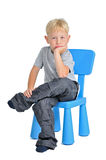 Trauriger Junge, der auf einem Stuhl sitzt Stockfotos