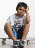Trauriger Junge, der auf seinem Skateboard sitzt Stockfoto