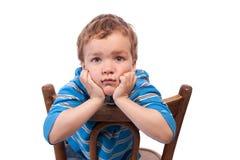 Trauriger Junge, der auf Stuhl sitzt Stockfotografie