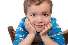 Trauriger Junge, der auf Stuhl sitzt Stockbild