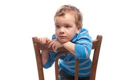 Trauriger Junge, der auf Stuhl sitzt Lizenzfreie Stockfotografie