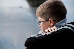 Trauriger Junge, der den Fluss betrachtet Lizenzfreie Stockfotografie