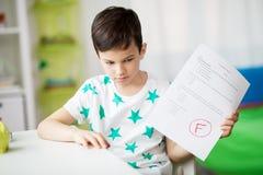 Trauriger Junge, der Schultest mit f-Grad hält lizenzfreie stockfotos