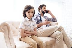 Trauriger Junge erhielt Umkippen wegen des Mangels an Aufmerksamkeit vom Vater lizenzfreie stockfotos