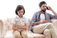 Trauriger Junge erhielt Umkippen wegen des Mangels an Aufmerksamkeit vom Vater stockfotos