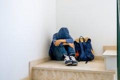 Trauriger Junge mit dem Rucksack, der allein in der Ecke im Treppenhaus sitzt stockfoto