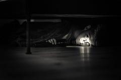 Trauriger Junge mit der Taschenlampe, die unter seinem Bett liegt Stockfotografie