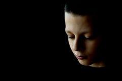 Trauriger Junge mit Träne in seinem Auge auf einem schwarzen Hintergrund Stockfotografie