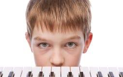 Trauriger Junge nahe Klaviertastatur Stockbild