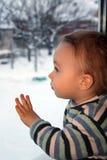 Trauriger Junge schaut durchdacht durch das Fenster Lizenzfreie Stockfotos