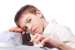 Trauriger Junge spielt Klavier Stockfotografie