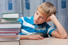 Trauriger Junge am Tisch mit einem Stapel Büchern Stockfoto