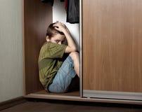 Trauriger Junge, versteckend im Wandschrank Stockfotografie