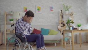 Trauriger junger asiatischer Mann sperrte in einem Athleten-Fußballspieler des Rollstuhls ehemaligen mit einem Fußball stock footage