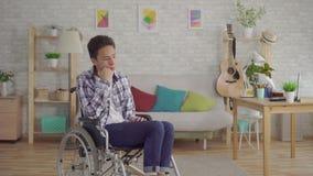 Trauriger junger asiatischer Mann sperrte in einem Rollstuhl im Wohnzimmer stock video footage