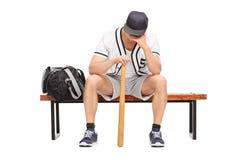 Trauriger junger Baseball-Spieler, der auf einer Bank sitzt Lizenzfreie Stockfotos