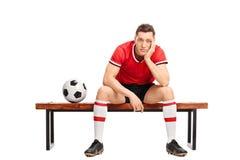 Trauriger junger Fußballspieler, der auf einer Bank sitzt Lizenzfreies Stockfoto