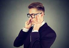 Trauriger junger Geschäftsmann mit dem besorgten betonten Gesichtsausdruck, der unten schaut lizenzfreie stockfotografie