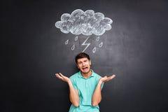 Trauriger junger Mann, der über Tafel mit gezogenem raincloud schreit Stockbild