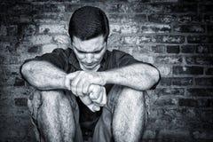 Trauriger junger Mann, der auf dem Boden mit einem Ziegelsteinhintergrund sitzt Stockbild