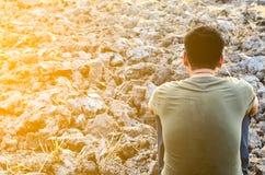 Trauriger junger Mann, der auf unfruchtbarem Boden sitzt Suchen Sie nach einem trockenen Reisfeld Lizenzfreie Stockbilder