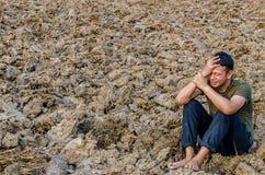 Trauriger junger Mann, der im unfruchtbaren Boden sitzt Stockbild