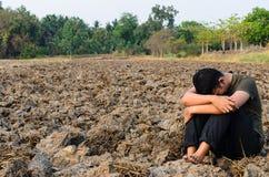 Trauriger junger Mann, der im unfruchtbaren Boden sitzt Stockbilder