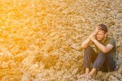 Trauriger junger Mann, der im unfruchtbaren Boden sitzt Mit Sun-Licht Stockfotografie