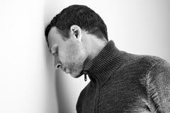 Trauriger junger Mann stand seinen Kopf auf Wand still Stockfotografie