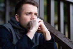 Trauriger kaukasischer Mann, der allein sitzt und über Probleme thinling stockfotos