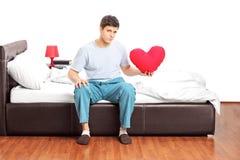 Trauriger Kerl, der allein auf Bett sitzt und ein Herz hält Stockfotos