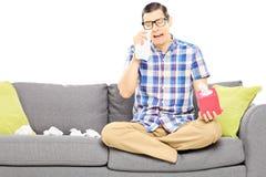 Trauriger Kerl, der auf einem Sofa sitzt und seine Augen vom Schreien abwischt Lizenzfreie Stockfotos